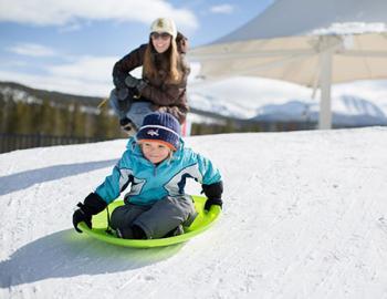 Boy sledding downhill.