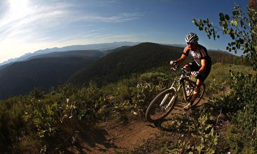 A solo bike races by a steep ridge while mountain biking in Colorado.