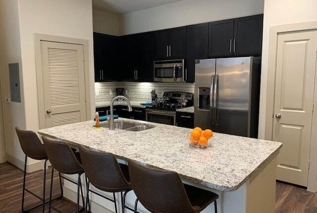 Full kitchen with fridge, oven, microwave and dining are on the island, from the Florida Design at Premier Patient Housing.