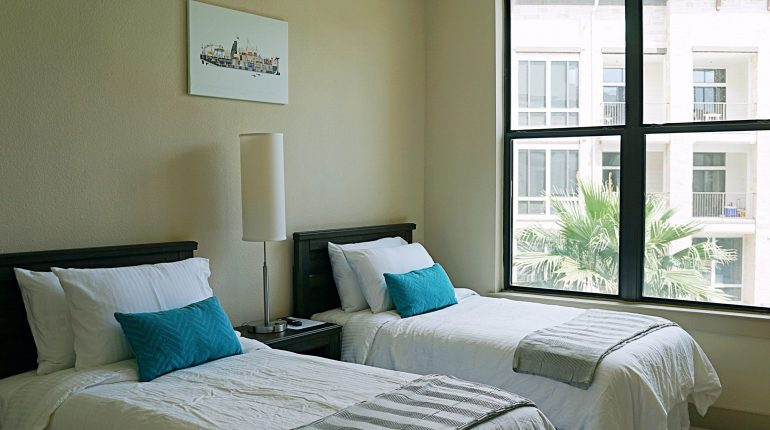 Doorway view of bedroom with two double beds from the California Design at Premier Patient Housing.