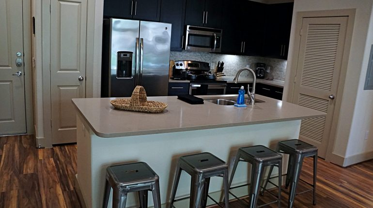 Full kitchen with fridge, oven, microwave and dining are on the island, from the Ohio design at Premier Patient Housing.