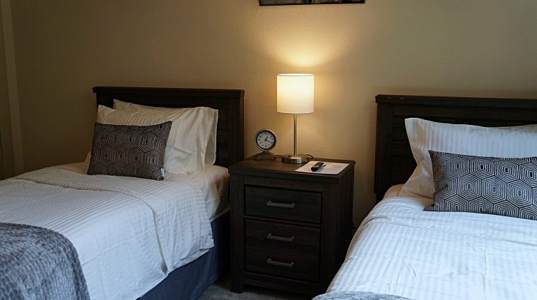 TV view of bedroom with two double beds from the Ohio design at Premier Patient Housing.