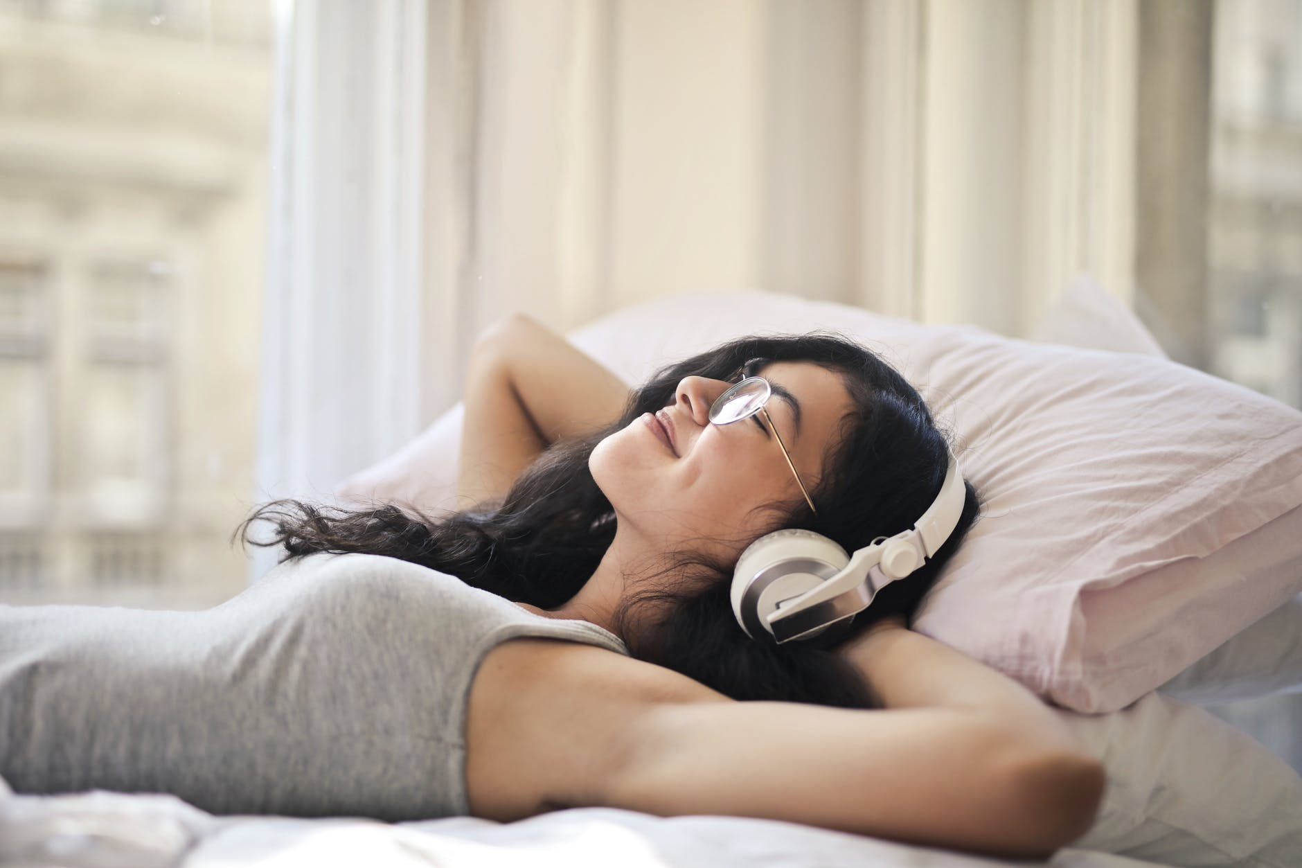 woman listening to soothing music on bed