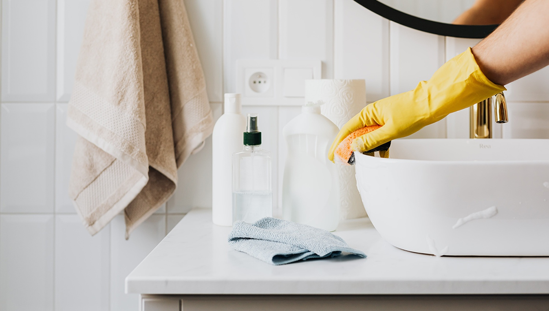 Cleaning bathroom counter. Photography by Karolina Grabowska @Pexels.