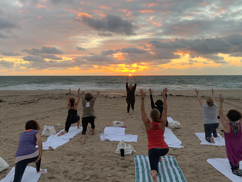 View of yoga class on the beach doing a lunge with their arms up