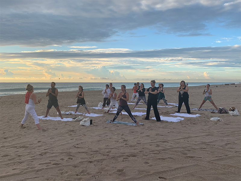 View of yoga class following their yoga instructor's pose
