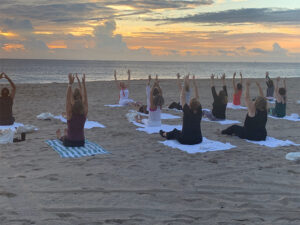 View of yoga class with their hands up in the air