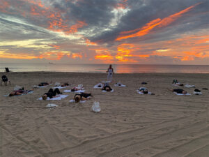 View of yoga class on the beach during sunset