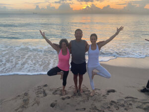 Two women and a man doing a yoga pose together