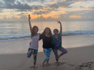 Three women doing yoga poses together