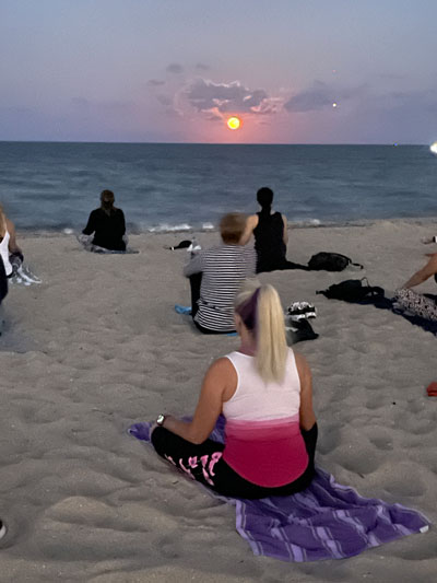 Ladies doing yoga on a beach at sun rise