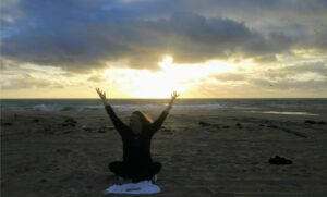 woman stretching her arms up to the sky