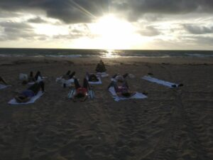 students laying on the beach as the sun goes down
