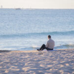 View of man sitting by the shore