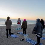 Woman teaching a class on the beach.