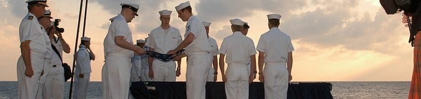 A group of navy men performing a full body burial at sea.