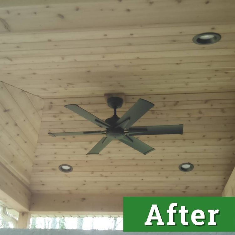 a black fan installed in a wood paneled ceiling