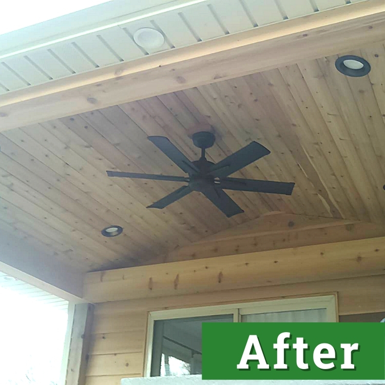 a black fan installed on a wood paneled ceiling with inset lighting