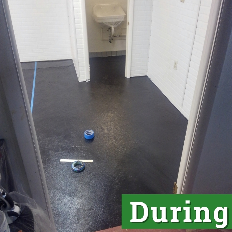a roll of blue tape rests on a black floor