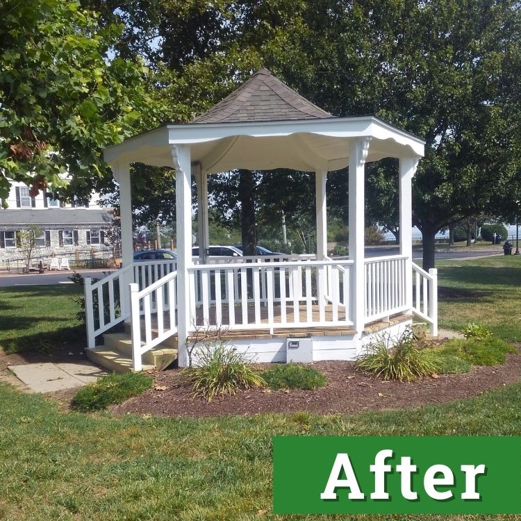 a newly painted white gazebo shines under the sun