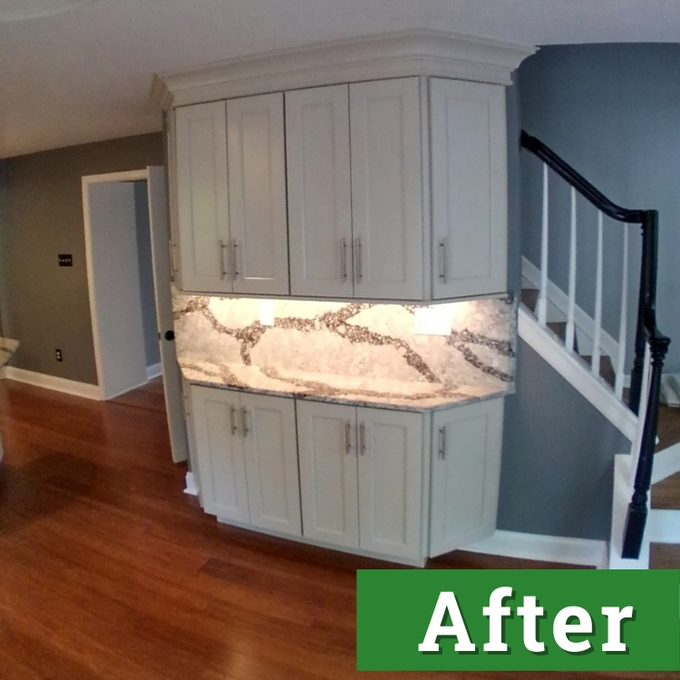 a built in cabinet with white doors and a white and black marble countertop