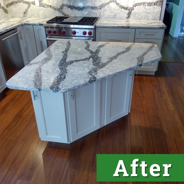 a kitchen island with white cabinets and a white and black marble countertop
