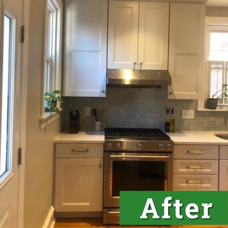 a new stainless steel oven and white cabinets