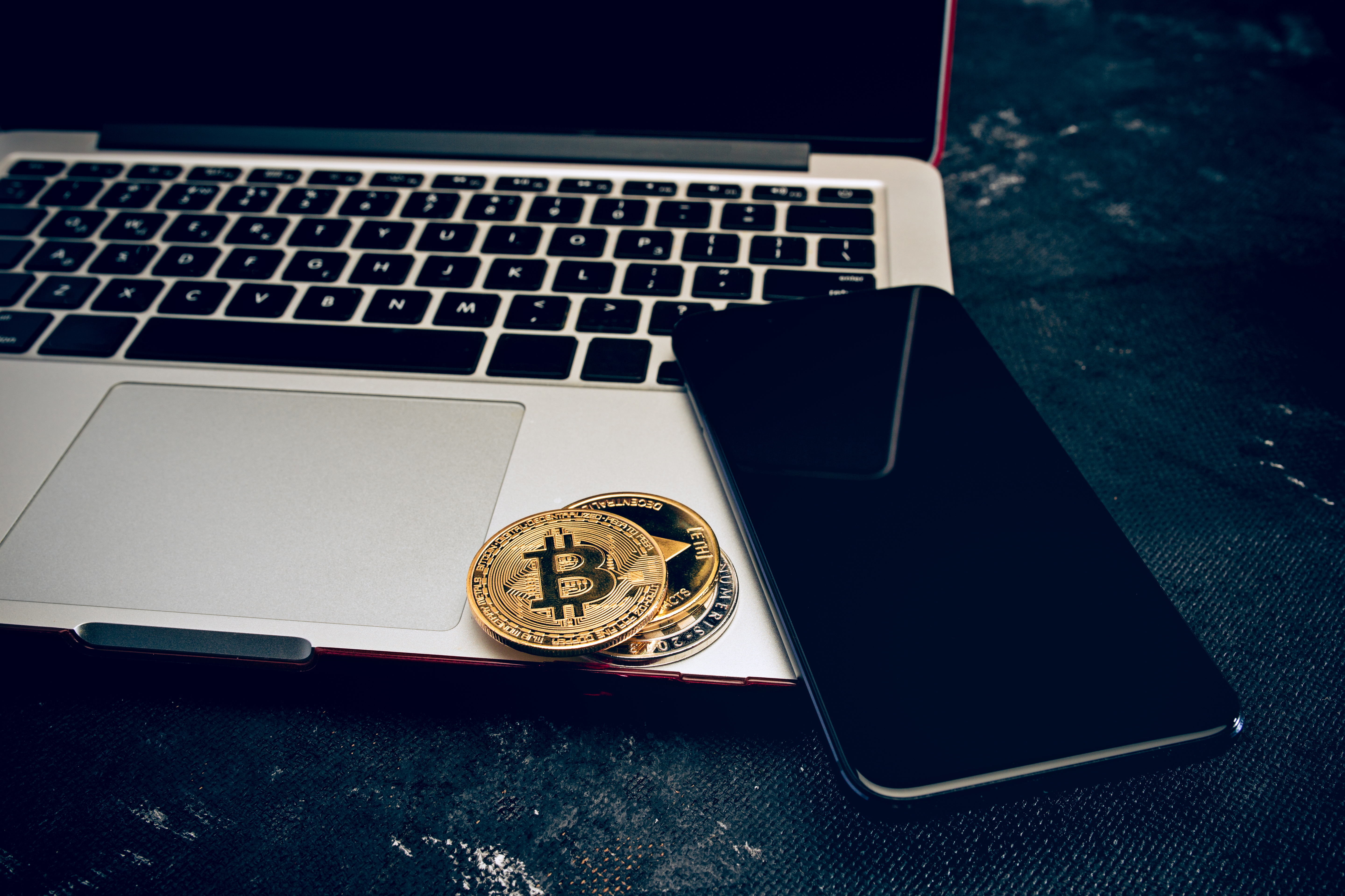 The golden bitcoin and mobile phone on keyboard. Cryptocurrency bitcoin coins. Litecoin, Bitcoin, Ethereum, e-commerce, busibess, finance concept. crypto currency symbol. virtual electronic money concepts