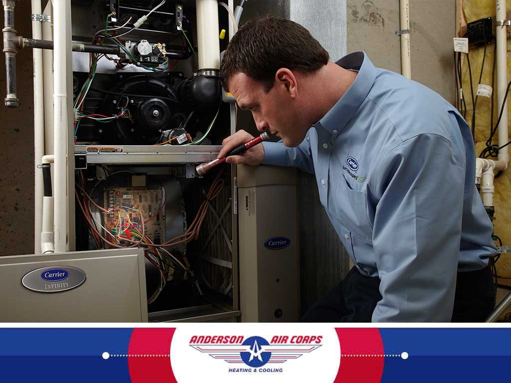 Anderson Air Corps employee fixing HVAC unit