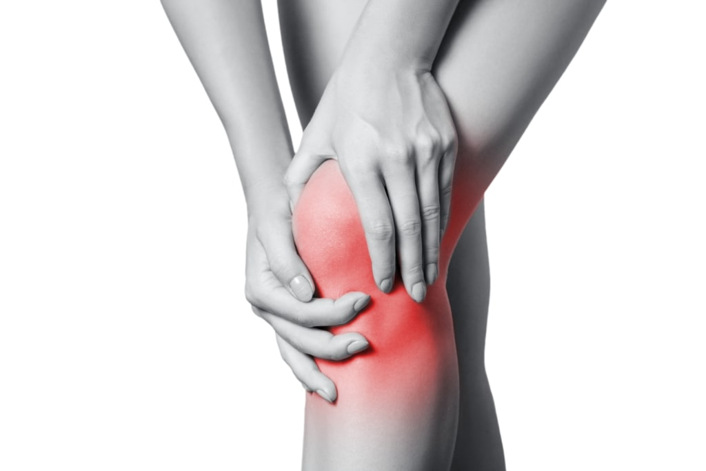 Person holding their knee in pain