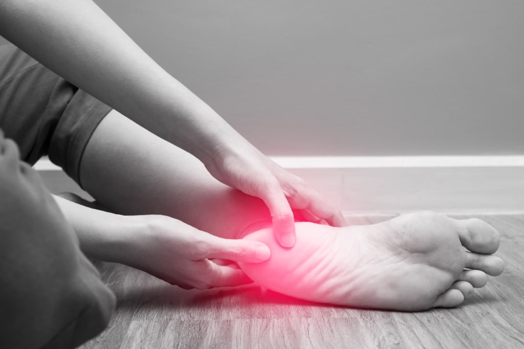 person holding their foot in pain