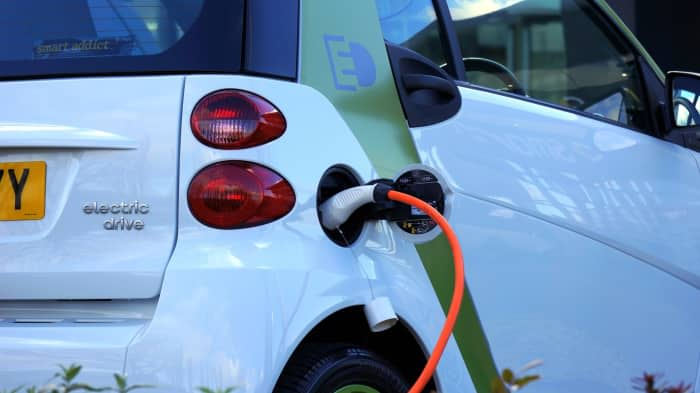 An electric Smart car plugged into a charging station