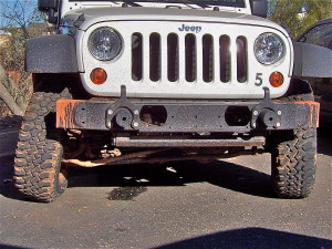Front end of a Jeep with a broken axle housing.