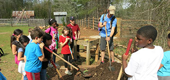 Students on a field trip to a farm are shown how to manually till earth by a volunteer.