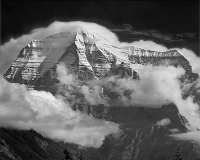"Clouds wreathe Mt. Robson, 12,972', 3954m, highest peak in the Canadian Rockies in Mt. Robson Provincial Park. Original is an 8x10 black and white negative using Tr-X film and a red filter, taken 8-18-1968 about 10 am. An 8x10 Eastman view camera and a 36"" Dallmeyer lens, weighing over 10 pounds, were used in a set-up requiring two tripods. Some burning and dodging was required to bring this print to completion. Copyright Ed Cooper, British Columbia."
