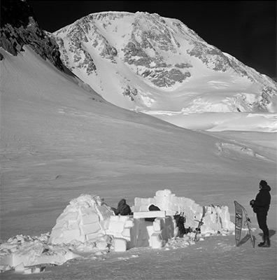 Igloo Camp at about 13,500' (4115m) at Windy Corner on Mt. Denali (was Mt. McKinley) 20,320' (6194m) June, 1958. Climber Fergus O'Connor is on the right. Copyright Ed Cooper Photo. Alaska.