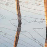 5. DHCA-SierraVly6-733-19-Barbed-Wire-Fence,-Three-Posts-and-Reflection-Detail,-Snowmelt-Fields,-Sierra-Valley,-Winter
