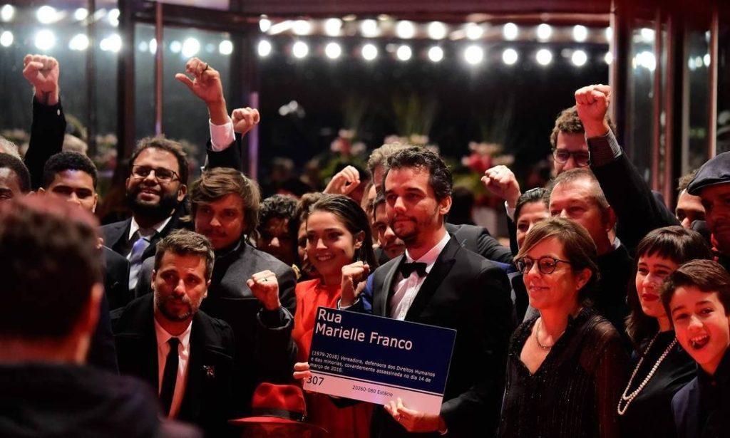 Wagner Moura levou uma placa em homenagem a Marielle Franco para o Festival de Berlim. Na foto, Moura aparece com a atriz Bella Camero (à esquerda, de vermelho), e o ator Bruno Gagliasso. (Foto: TOBIAS SCHWARZ / AFP)