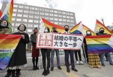 Manifestantes em Saporo (Japão) erguem cartaz que diz 'decisão inconstitucional' em frente a tribunal que decidiu pela legalidade da união entre pessoas do mesmo sexo, em foto de 17 de março de 2021. (Foto: Kyodo/via Reuters)