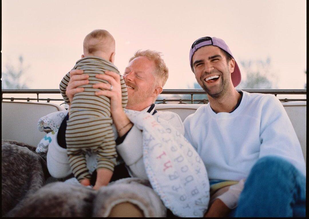 Jesse Tyler Ferguson carrega o pequeno Tyler; à direita, o marido do ator, Justin Mikita. Foto: Reprodução/Instagram)