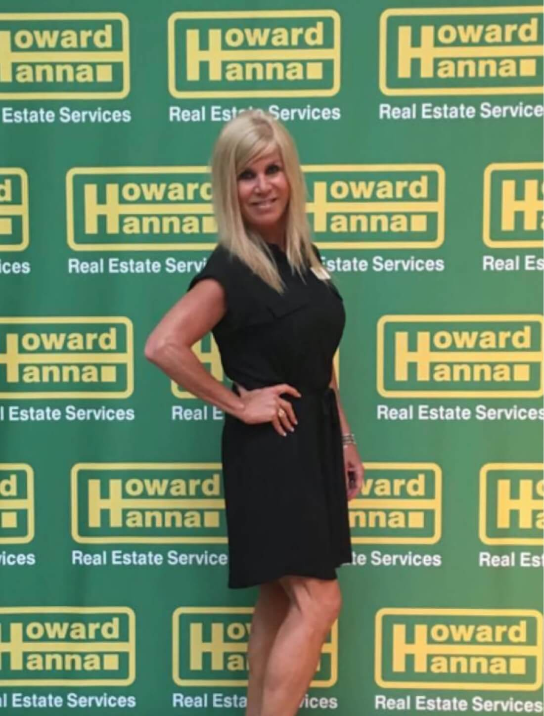Donna Littlefield posing in front of Howard Hanna Real Estate Services banner