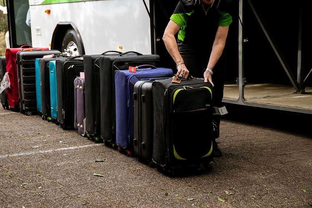 coolum coach employee preparing luggage to be carried onboard