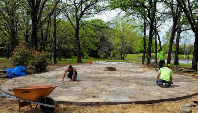 workers laying flagstone sitting area