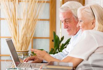View of two senior citizens enjoying TV & Internet in Senior Living