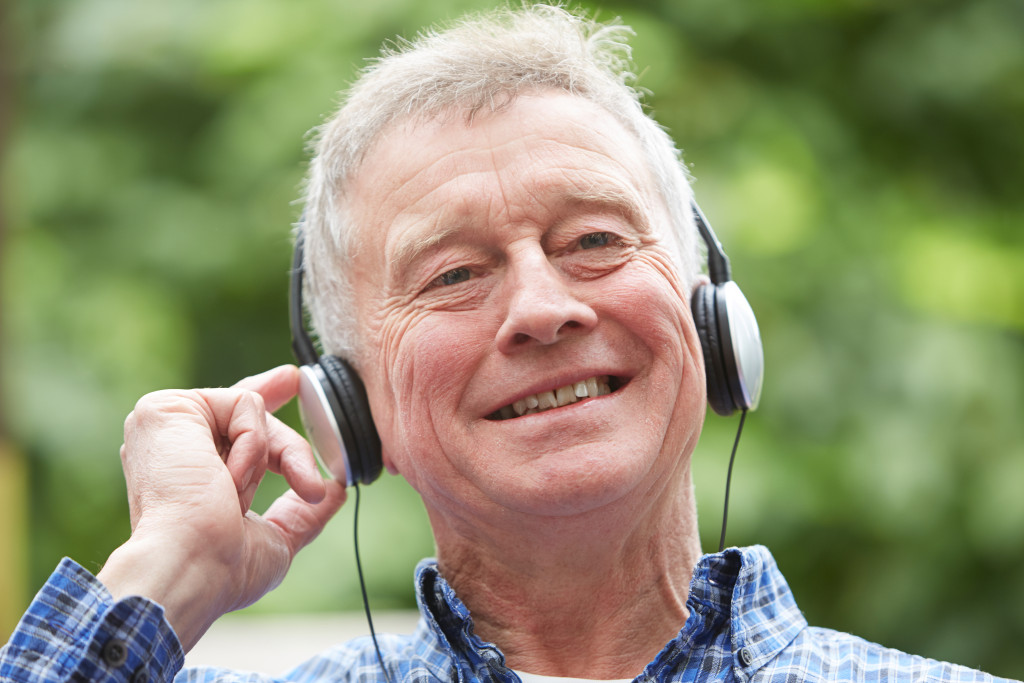 Senior Man Relaxing Listening To Music On Headphones In Garden