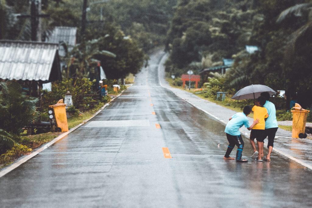 Boys running back home in the rain.