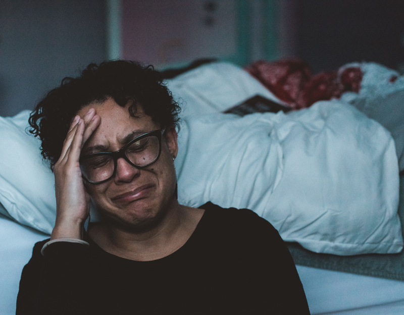 Depression/Anxiety/OCD brown skinned female with black short curly hair and black glasses crying on the floor next to a bed.
