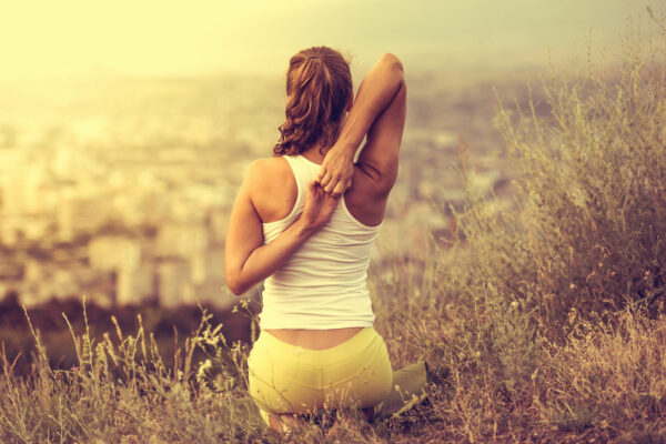 Young woman sitting on her knees, facing away, and stretching while looking out over a city in the distance.