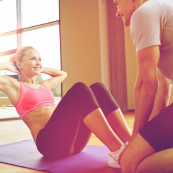Fit woman doing sit ups with personal trainer in a gym.