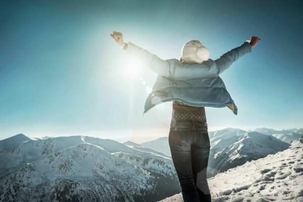 Woman expressing happiness on top of a snow capped mountain